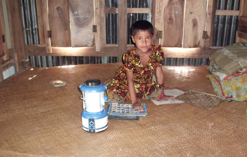 A child is studying using a Solar Lantern, provided under the ENRICH. Her household does not have electricity supply from the national gride
