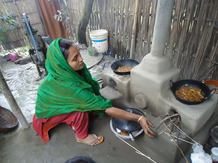 An ENRICH participant is using a health & environment-friendly cooking stove