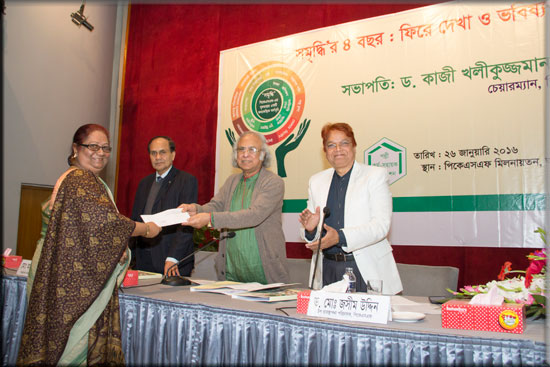 An Executive Director of an ENRICH implementing Partner Organization receiving a cheque of ENRICH programme