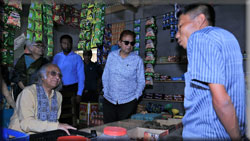Udayan Chakma, a rehabilitated beggar, narrating his story to PKSF Chairman as Dr Jashim Uddin looks on at Udayan's grocery shop in Panchhari of Khagrachhari