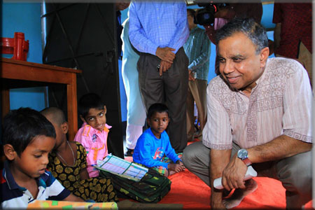 Md Abul Kalam Azad, Chief Coordinator for SDG Affairs, is talking to a child at an ENRICH Education Assistance Centre